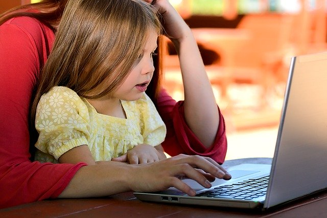 holčička sedící s matkou u počítače